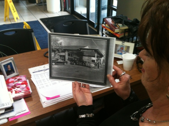 Sales Consultant Darlene Roberts holds up a picture of her grandfather's Studebaker dealership once located near Lancaster, Ohio
